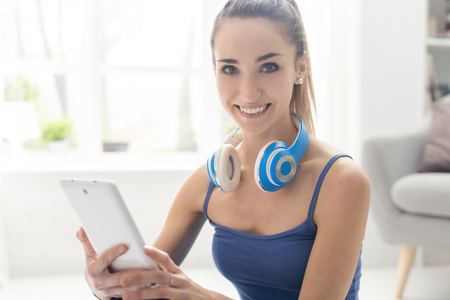 Happy sporty woman with headphones, she is searching music online using her digital tablet