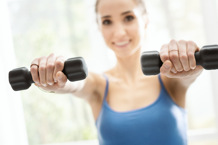 Young smiling woman exercising at home next to a window, she is lifting dumbbells, fitness and sports concept