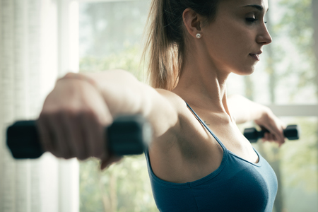 Young sporty woman exercising at home with dumbbells, fitness and sports concept Stock Photo