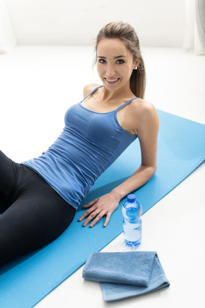 Happy young woman exercising: she is having a break, lying down on a mat and smiling at camera, fitness and sports concept