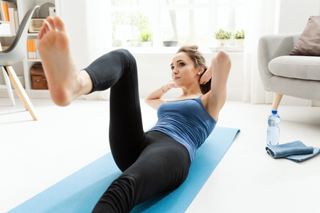 Young fit woman doing sit ups and exercising on the floor at home in the living room, fitness and sports concept
