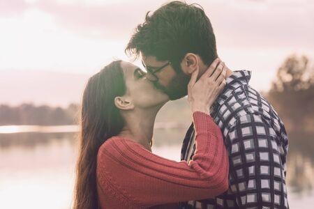 Giovani coppie romantiche che si baciano all'aperto al lago, concetto di gioventù e relazioni