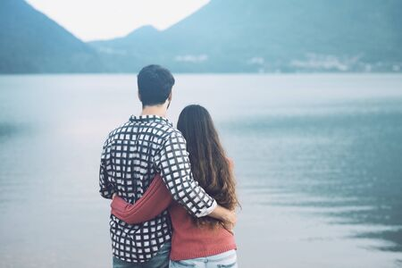 Giovani coppie romantiche che abbracciano e guardano il concetto del lago, delle relazioni e dei sentimenti Archivio Fotografico