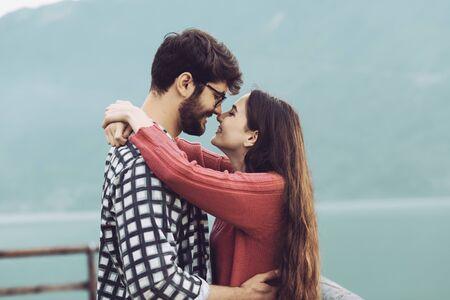 Romantisches junges Paar am See, sie umarmen und lächeln, Liebes- und Beziehungskonzept