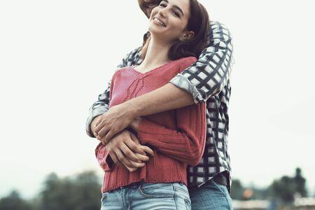 Giovani coppie felici che trascorrono del tempo insieme all'aperto, si abbracciano e sorridono Archivio Fotografico