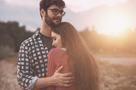 Giovani coppie amorose che si abbracciano all'aperto, alberi e natura sullo sfondo