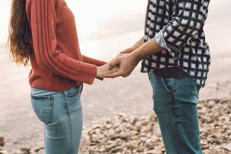 Dulce pareja joven pasar tiempo juntos en el lago, están tomados de la mano