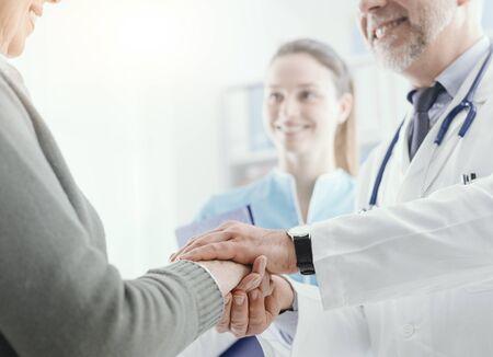 Medico professionista che aiuta e sostiene un paziente anziano, le tiene le mani, l'assistenza sanitaria e il concetto di geriatria