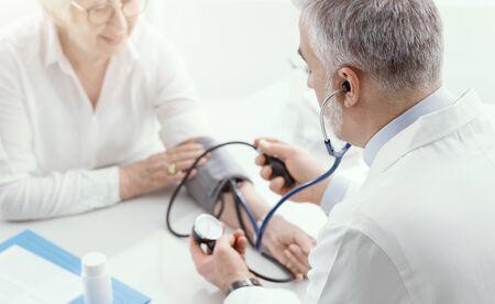 Médico profesional que mide la presión arterial de una paciente mayor durante una visita, concepto de hipertensión y prevención