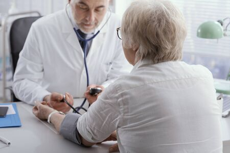 Professional doctor measuring blood pressure of a senior female patient during a visit, hypertension and prevention concept