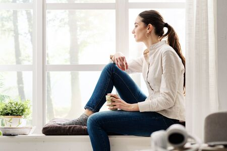 Young woman relaxing at home next to a window and having a cup of coffee
