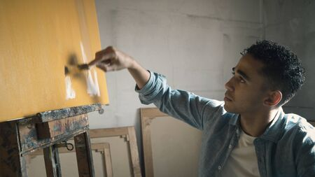 Young creative artist working in the studio, he is painting on canvas, art and talent concept Imagens - 133371414