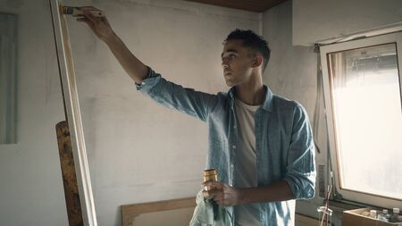 Young creative artist painting on canvas in the studio, he is holding a brush and a jar with paint Imagens - 133371437