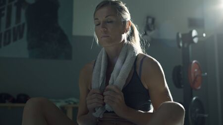 Woman having a break after working out at the gym, she is holding a towel behind her neck, fitness and sports concept