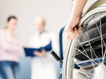 Patient in wheelchair at the hospital, a woman and the doctor are discussing in the background, hand on wheel close up