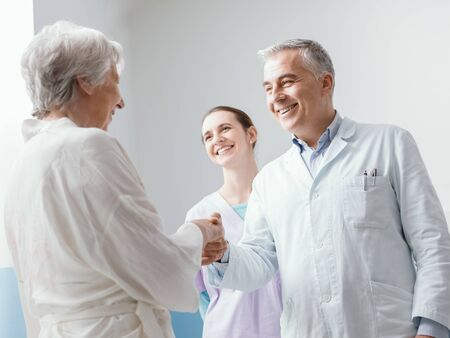 Smiling professional doctor and nurse meeting a senior patient at the clinic, they are shaking hands and welcoming her