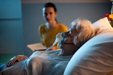 Mujer en el hospital ayudando a un paciente mayor con máscara de oxígeno por la noche, ella está leyendo un libro y revisándola