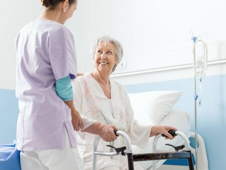 Smiling professional nurse assisting a senior patient at the hospital Imagens