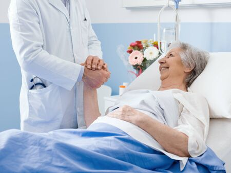 Doctor visiting a hospitalized elderly patient at the hospital