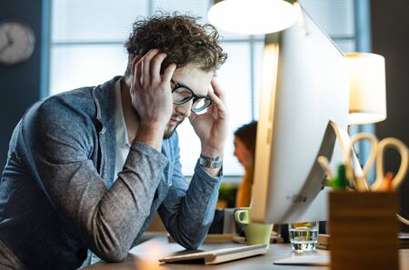 Stressed office worker sitting at desk and working with his computer, he is tired and having a headache Stock Photo