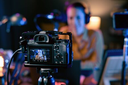 Young vlogger recording a video in her studio, professional camera in the foreground
