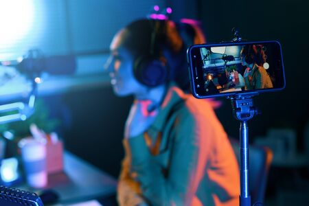 Young woman streaming a live video with her smartphone and talking into a microphone in the studio Stock Photo