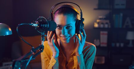 Young smiling woman wearing headphones and talking into a microphone at the radio station, entertainment and communication concept Archivio Fotografico