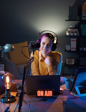 Young smiling radio host talking into a microphone and broadcasting at the radio station, entertainment and communication concept