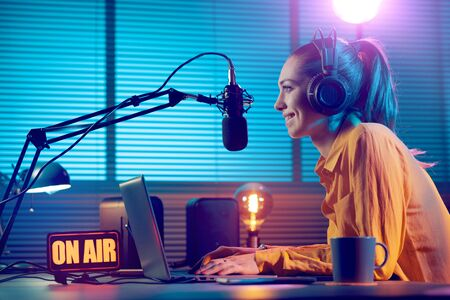 Young radio host working in the studio, she is smiling and broadcasting announcements Stock Photo