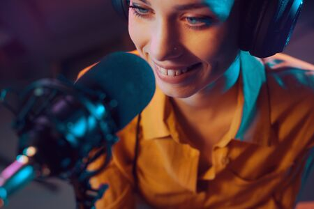 Young smiling host at the radio broadcasting station, communication and entertainment concept Stockfoto