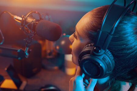 Young charming radio dj working in the studio, she is talking into the microphone, entertainment and communication concept