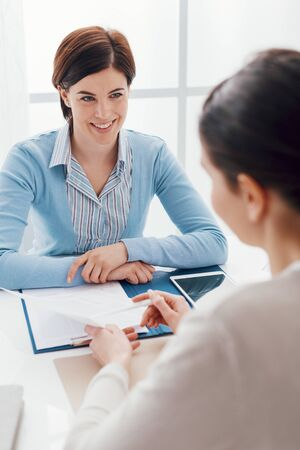 Business meeting in the office: a businesswoman is talking and checking a contract with the customer