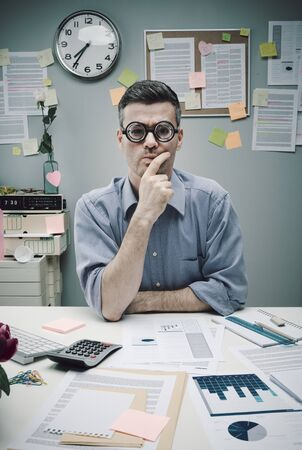 Pensive nerd businessman at office with hand on chin. Banque d'images