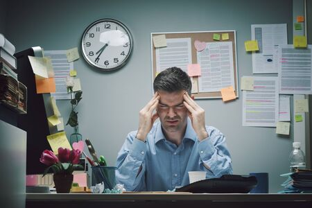 Müder Büroangestellter am Schreibtisch mit Kopfschmerzen, die seine Schläfen berühren. Standard-Bild