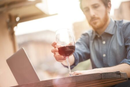 Young man sitting at outdoor bar table having a glass of red wine and using his laptop