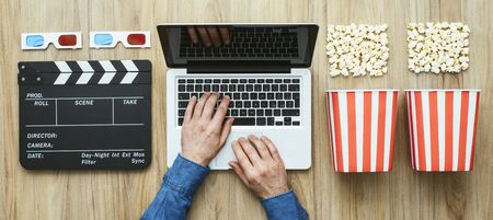 Man watching a film streaming online with popcorn, 3D glasses and clapboard, cinema and entertainment concept, flat lay Banco de Imagens