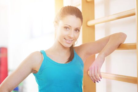 Attractive smiling woman at gym leaning against wood wall bars.