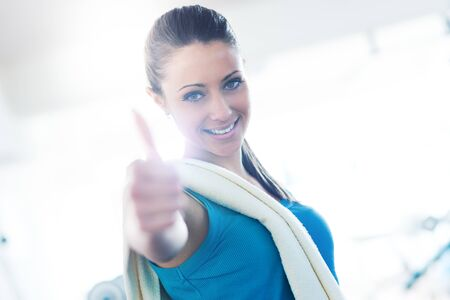 Attractive young woman with towel at gym smiling at camera thumbs up. Фото со стока