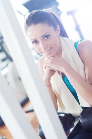 Attractive smiling woman at gym relaxing on exercise machine bench.