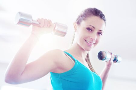 Young attractive woman smiling and working out with dumbbells.