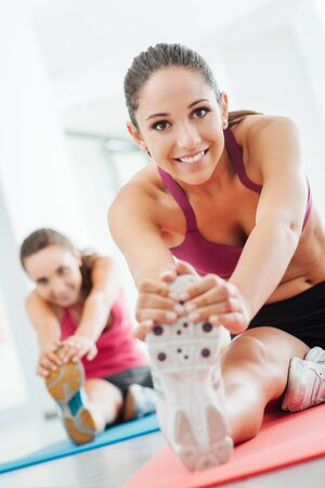 Smiling young women at the gym doing a stretching exercise for legs on a mat, fitness and health concept