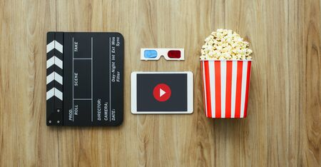 Clapper board, digital tablet, 3D glasses and popcorn on a wooden surface, cinema and entertainment concept, flat lay