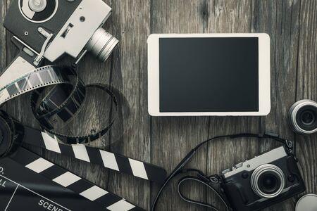 Vintage film camera, tablet, clapper board, filmstrip and old camera on a desktop, cinema and videomaking concept