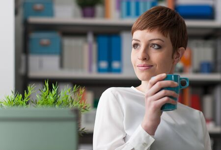 Attractive smiling young woman having a coffee break and holding a cup Фото со стока
