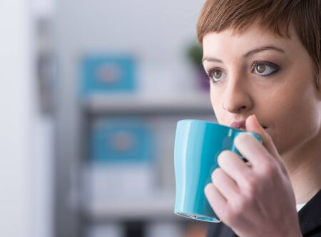 Attractive young woman having a coffee break and holding a cup, she is looking away and thinking Фото со стока