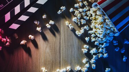 Popcorn and clapper on a wooden desktop, dramatic lighting, cinema and movies concept