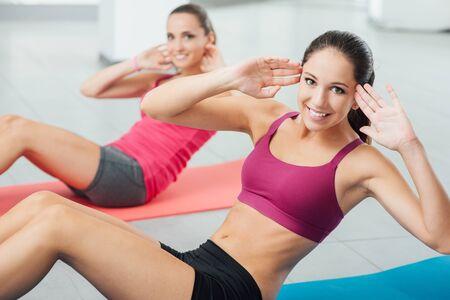 Donne sorridenti che si esercitano in palestra su un tappetino e guardano la fotocamera, il fitness e il concetto di allenamento