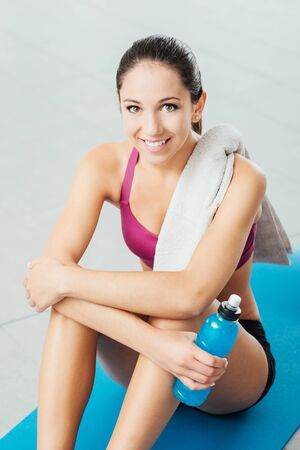 Smiling young beautiful woman sitting on a mat and relaxing after workout, she is looking at camera