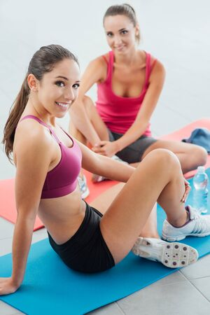 Young smiling girls at the gym sitting on mats and having a break after workout, they are looking at camera