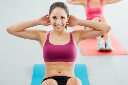 Sporty young girl at the gym doing abdominals workout on a mat, she is smiling at camera, fitness and health concept